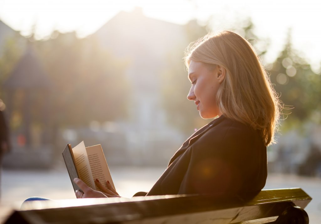 Young girl reads a book at a park