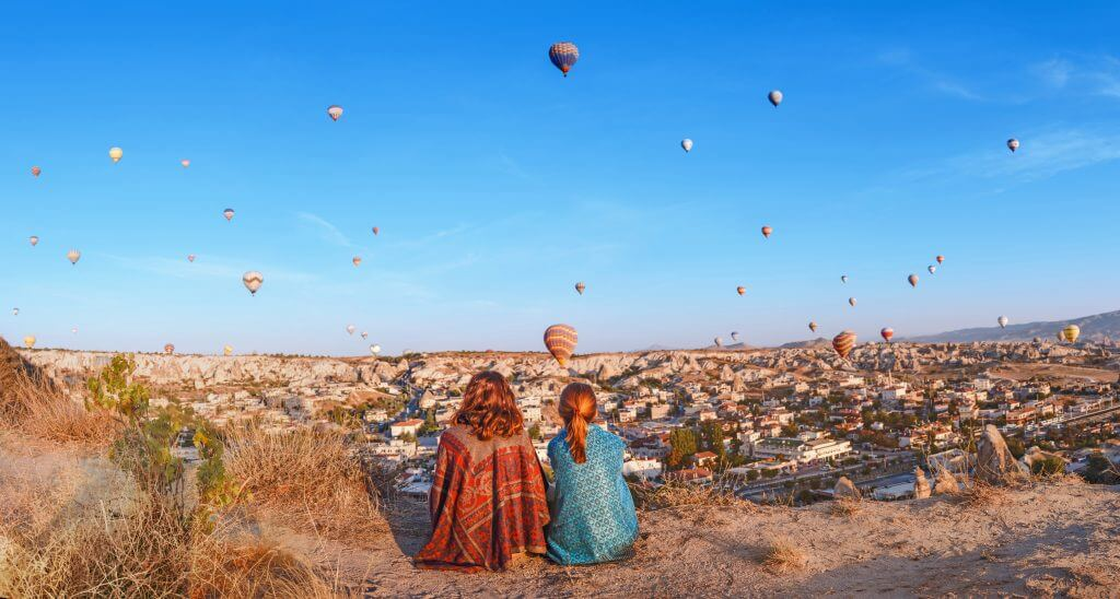 Two friends are looking at air balloons in Turkey